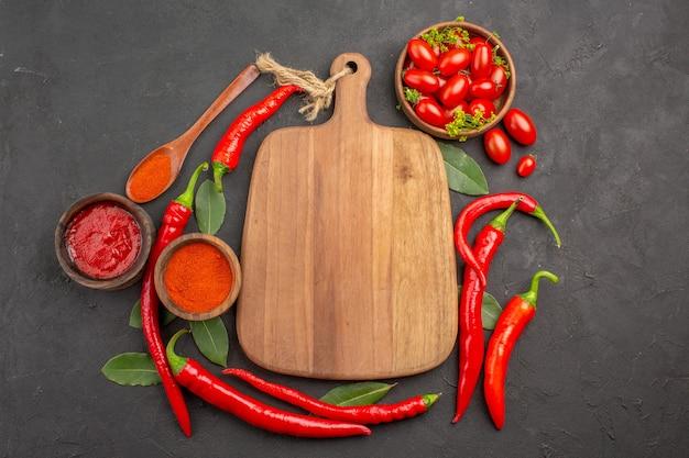 上面図まな板の上のチェリートマトの赤唐辛子のボウル木のスプーンの月桂樹の葉と黒いテーブルの上のケチャップと唐辛子の粉のボウル