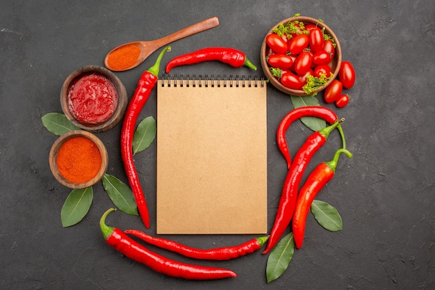 上面図チェリートマトのボウル、赤唐辛子、ノートブック、木のスプーンの月桂樹の葉、黒いテーブルにケチャップと唐辛子の粉末のボウル