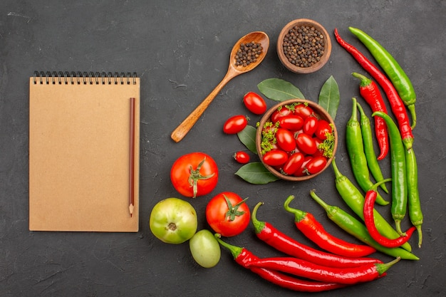 Вид сверху миска с помидорами черри острый красный перец черный перец в деревянной ложке миска с черным перцем и блокнот на черном фоне