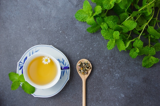 ミントの葉とスプーンでカモミールハーブとカモミールティーのカップを平面図します。