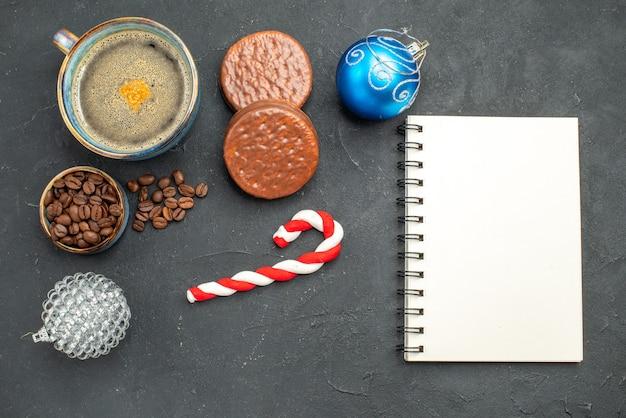 Вид сверху чашку кофе с семенами кофе, печенье, рождественские детали записной книжки на темном изолированном фоне