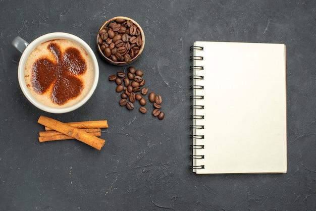 上面図コーヒーの種とコーヒーボウルのカップシナモンは暗い孤立した背景にメモ帳を貼り付けます