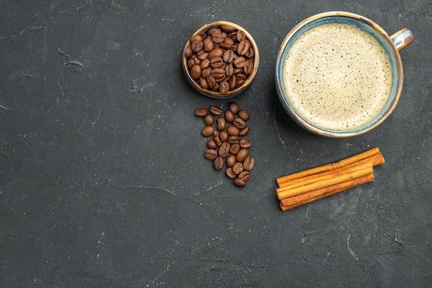 暗い孤立した背景にコーヒーの種シナモンスティックとコーヒーボウルの上面図