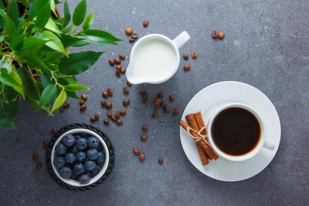 Вид сверху чашка кофе с черникой, сухой корицы, растений, молока на серой поверхности. горизонтальный