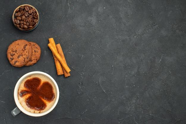 Вид сверху чашка кофе с семенами кофейных зерен, палочками корицы и печеньем на темном изолированном фоне