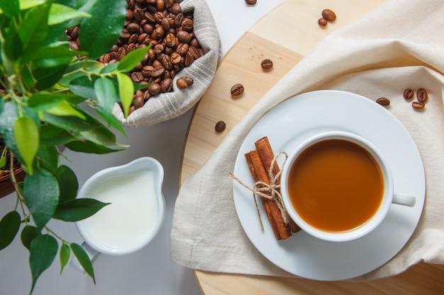 Вид сверху чашка кофе с кофе в зернах в мешок, растение, молоко, сухая корица на платформе и белая поверхность по вертикали