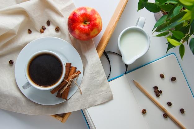 Взгляд сверху чашка кофе с молоком, яблоком, сухой циннамоном, заводом, карандашем и тетрадью на белой поверхности. горизонтальный