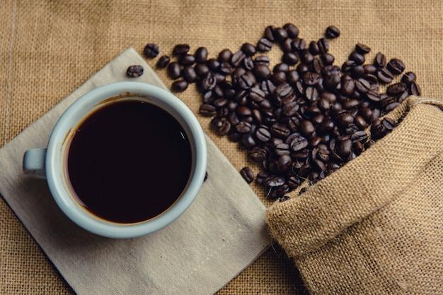 Вид сверху чашка горячего кофе, кофейные зерна на фоне мешка