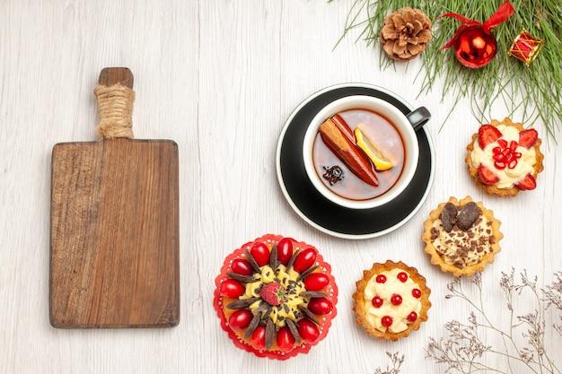 Вид сверху чашка лимонного чая с корицей, пирожные с ягодными пирогами и сосновые листья с рождественскими игрушками и разделочной доской на белой деревянной земле
