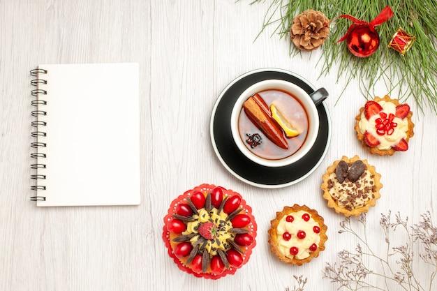Вид сверху чашка лимонного чая с корицей, пирожные с ягодным пирогом и сосновые листья с рождественскими игрушками и блокнотом на белой деревянной земле