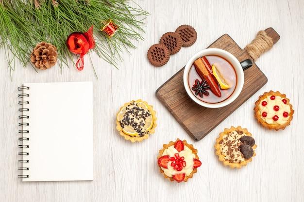 Вид сверху чашка чая с лимоном и корицей на разделочной доске, печенье и листья сосны с рождественскими игрушками и блокнотом на белой деревянной земле