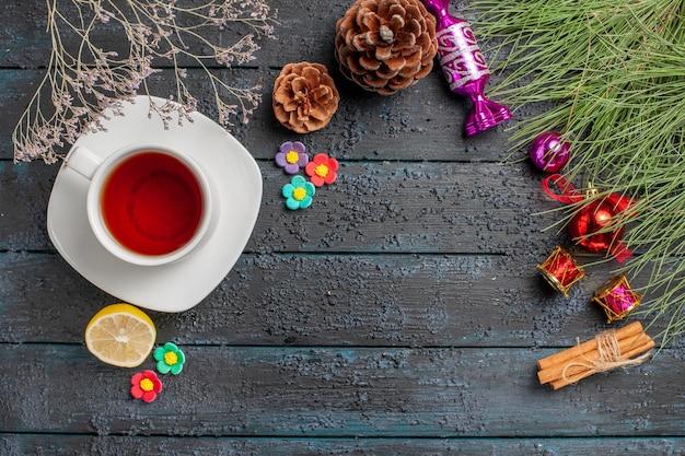 레몬 시나몬 스틱 옆에 있는 흰색 접시에 있는 차 한 잔은 테이블에 크리스마스 장난감과 원뿔이 있는 가문비나무 가지를 꽂습니다.