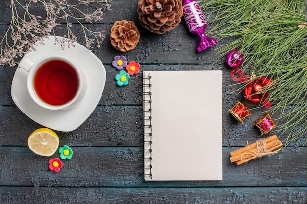 흰색 노트북 레몬 계피 스틱 옆에 있는 흰색 접시에 있는 차 한 잔은 회색 배경에 크리스마스 장난감과 원뿔이 있는 가문비나무 가지를 꽂습니다.