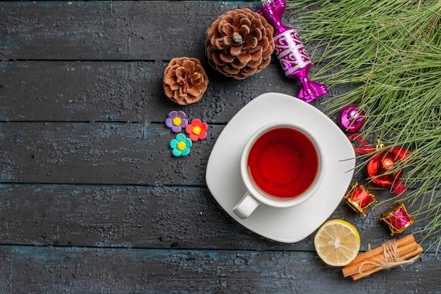 테이블 오른쪽에 크리스마스 장난감과 콘이 있는 계피 레몬 가문비나무 가지 옆에 있는 흰색 접시에 있는 차 한 잔