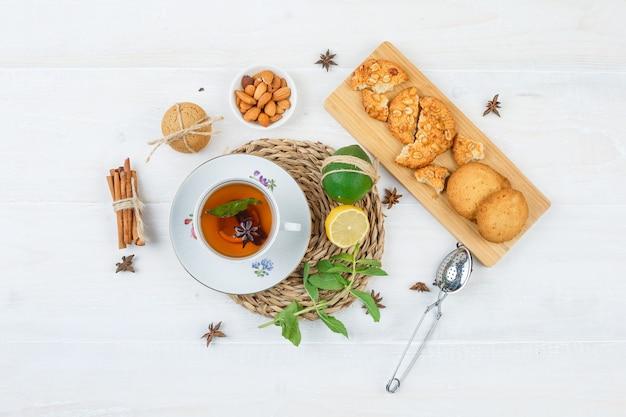 Вид сверху чашка чая, цитрусовые и листья мяты на круглой подставке с печеньем на разделочной доске
