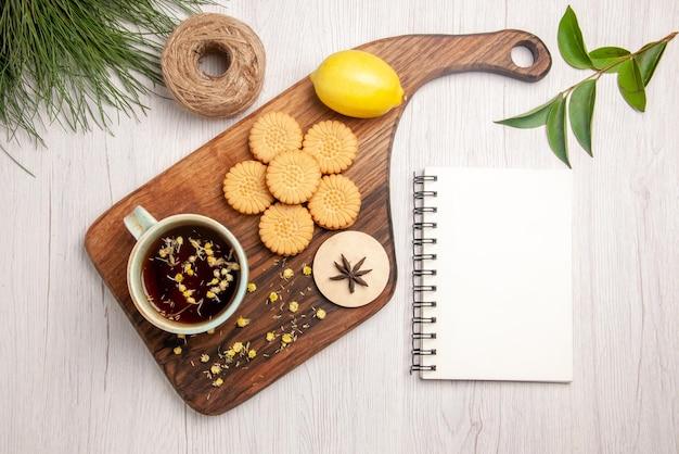 흰색 공책과 크리스마스 나무 가지 옆에 있는 나무 판자에 있는 차 쿠키 레몬 스타니스 한 잔의 위쪽 전망