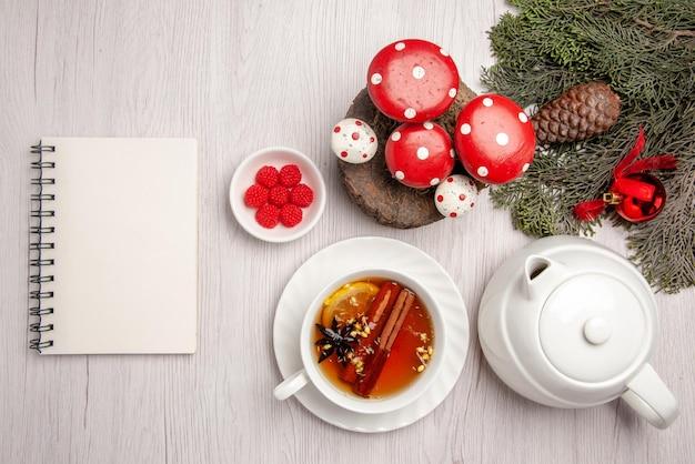 찻주전자 옆에 있는 컵에 레몬과 계피가 든 차 허브 차 한 잔과 테이블에 콘과 크리스마스 트리 장난감이 있는 크리스마스 트리 가지