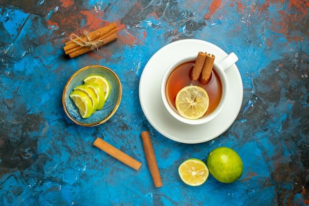 Вид сверху чашка чая с лимоном на синей красной поверхности