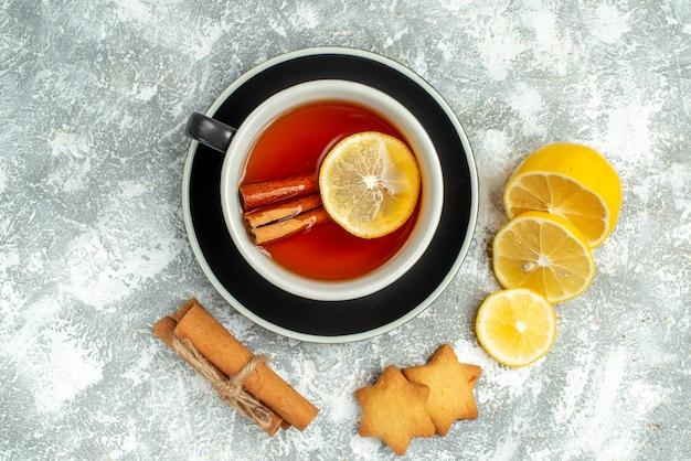 Вид сверху чашка чая, ломтики лимона, палочки корицы, печенье на серой поверхности со свободным пространством