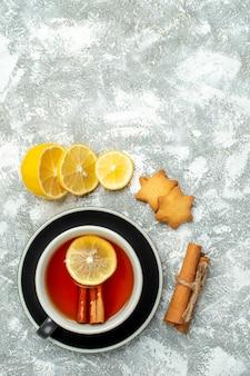 Вид сверху чашка чая, ломтики лимона, палочки корицы на серой поверхности, свободное пространство
