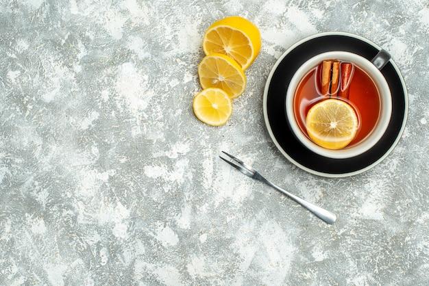 Вид сверху чашка чая с ломтиками лимона на серой поверхности свободного пространства