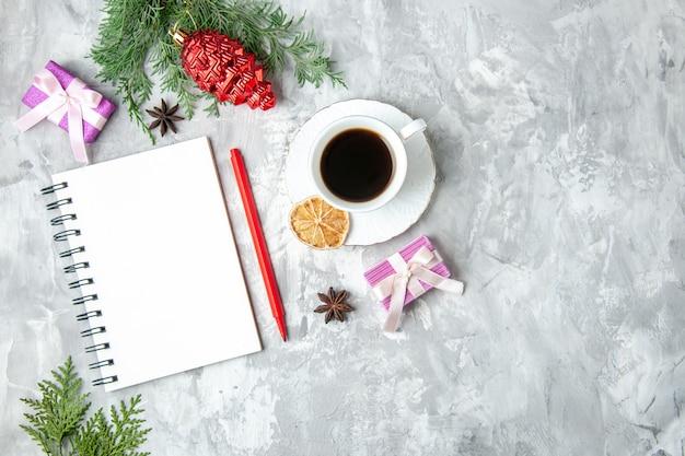 灰色の背景にお茶のノートブック鉛筆小さなギフトクリスマスツリーのおもちゃのカップを上面図