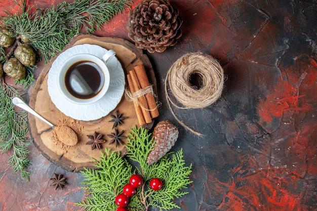 나무 판자에 있는 차 한 잔의 상위 뷰는 어두운 배경에 있는 솔방울 아니스 짚 실을 스틱 계피 스틱