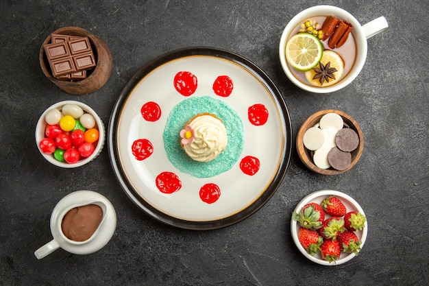 Вид сверху чашка чая, тарелка аппетитного кекса, чашка чая с звездчатым анисом и лимоном и миска шоколадных конфет и клубники на черном столе