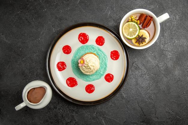 빨간 소스를 곁들인 식욕을 돋우는 컵케이크의 차 접시와 검은 탁자에 있는 차 한 잔과 초콜릿 크림 한 그릇