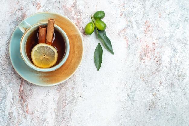 上面図一杯のお茶白い一杯のお茶とレモンとシナモンのスライスが受け皿にあり、ピンクのテーブルに柑橘系の果物があります