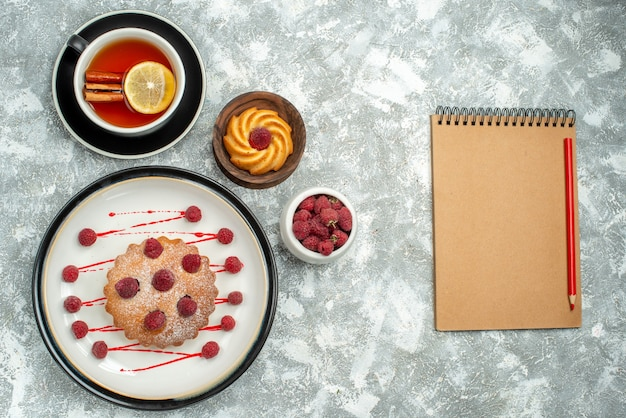 회색 표면에 타원형 접시 노트북에 레몬 조각과 계피 베리 케이크와 함께 차 한잔 상위 뷰