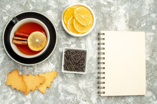 上面図レモンスライスとシナモンスティックビスケットボウルと灰色の表面にチョコレートノートブックとお茶のカップ