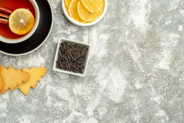 上面図レモンスライスとシナモンスティックビスケットボウルとチョコレートの灰色の表面のコピーの場所にお茶のカップ