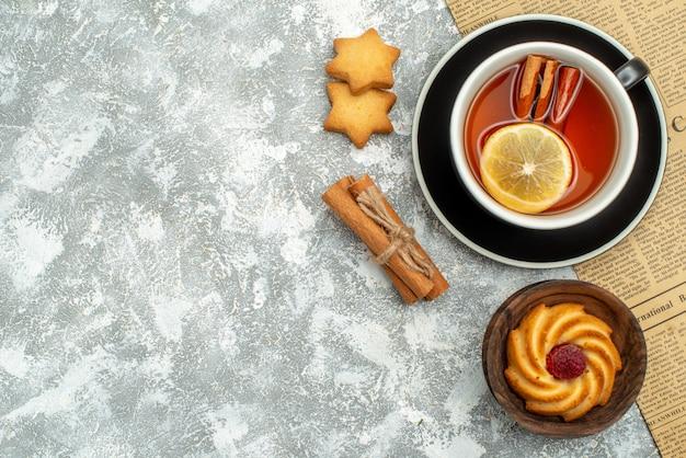 Вид сверху чашка чая с ломтиками лимона и палочками корицы на газетном печеньке болезнь корицы на серой поверхности