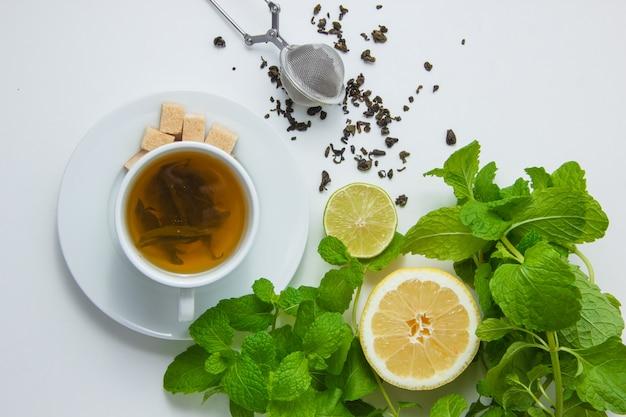 상위 뷰 레몬, 설탕, 민트와 차 한 잔 흰색 표면에 나뭇잎. 수평