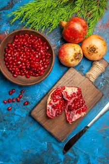 도마 위에 있는 잘린 석류 디너 나이프, 그릇에 석류 씨앗, 파란색 배경에 석류