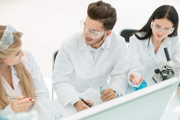 Top view.실험실에서 컴퓨터 작업을 하는 과학자 그룹입니다. 과학과 건강