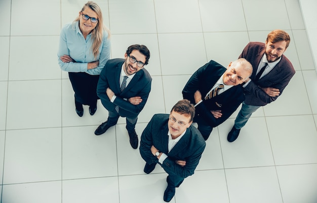 Вид сверху. группа улыбающихся деловых людей смотрит в камеру