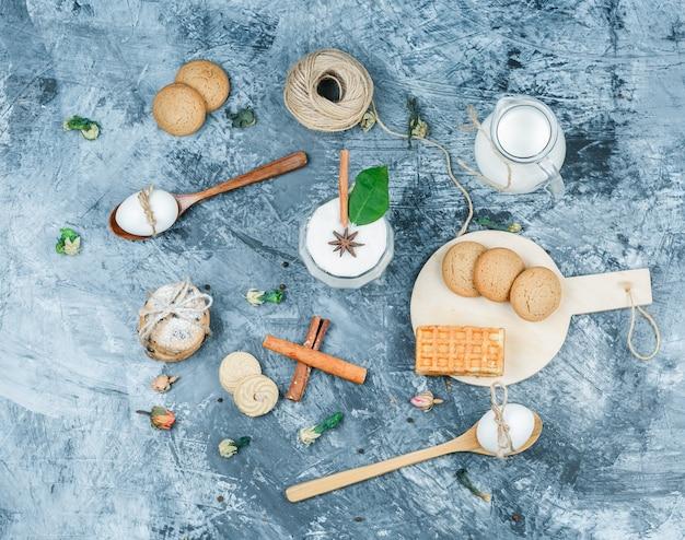 上面図牛乳の水差しとヨーグルトのガラスのボウル、スプーン、木の板にクッキー、紺色の大理石の表面に卵、クルー、シナモン。水平