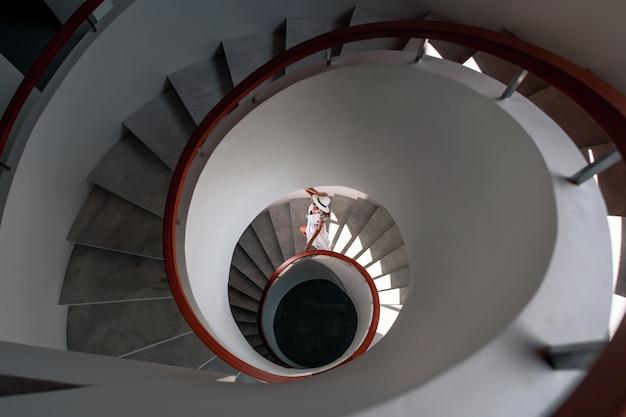 상위 뷰 : 흰색 드레스와 흰색 모자를 입은 고급스러운 소녀가 흰색 나선형 계단 아래로 내려갑니다.