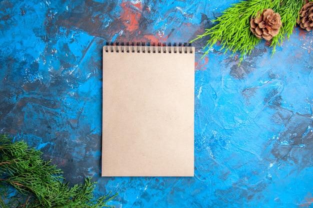 青赤の背景にノートブックの松の木の枝と円錐形の上面図