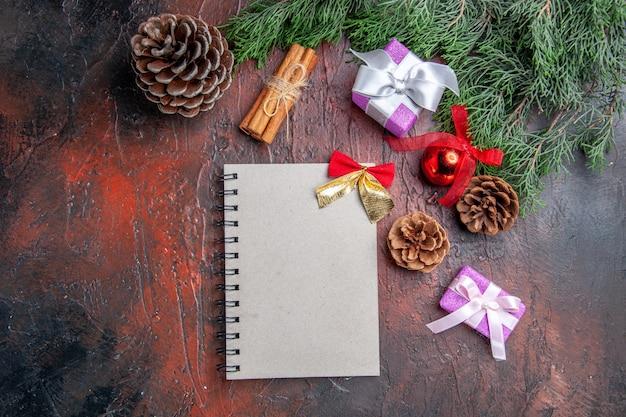 小さな弓の松の木の枝の円錐形のクリスマスツリーのおもちゃと濃い赤の背景にシナモンの贈り物とノートブックの上面図