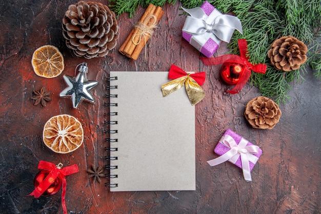 小さな弓の松の木の枝の円錐形のクリスマスツリーのおもちゃとギフトシナモンスティック乾燥レモンスライスと濃い赤の背景のノートブックの上面図