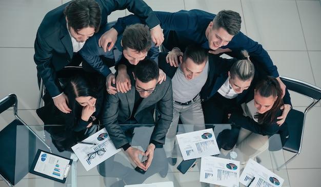 上面図。机に座ってカメラを見ている成功したビジネスチーム。