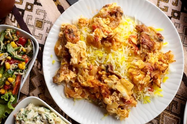トップビュー伝統的なアゼルバイジャン料理chyhyrtmaピラフフライドチキンのオムレツとご飯