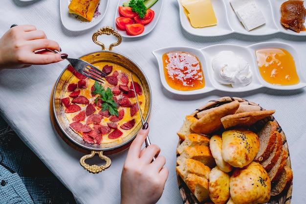 トップビューパンのバスケットとフライパンでソーセージと朝食のオムレツを持つ女性