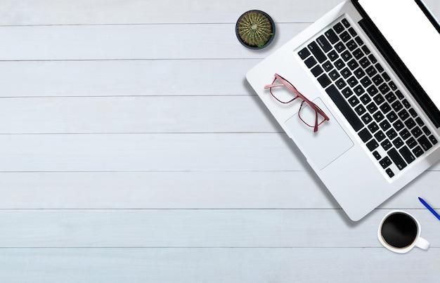 Вид сверху над компьютерным ноутбуком на белом деревянном полу в офисном стиле.