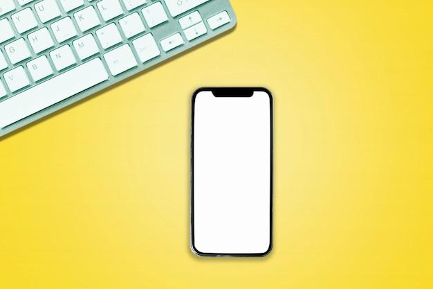 オフィススタイルの白黄色の背景に電話コンピュータノートブックの上の上面図