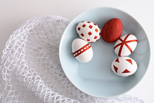 Top view abstract easter eggs with red geometric patterns in blue plate on white mesh eco bag