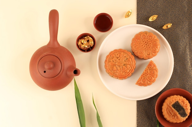 Top view abstract still life mid autumn festival snack moon cake on cream  background with young bamboo tree, selected focus, copy space